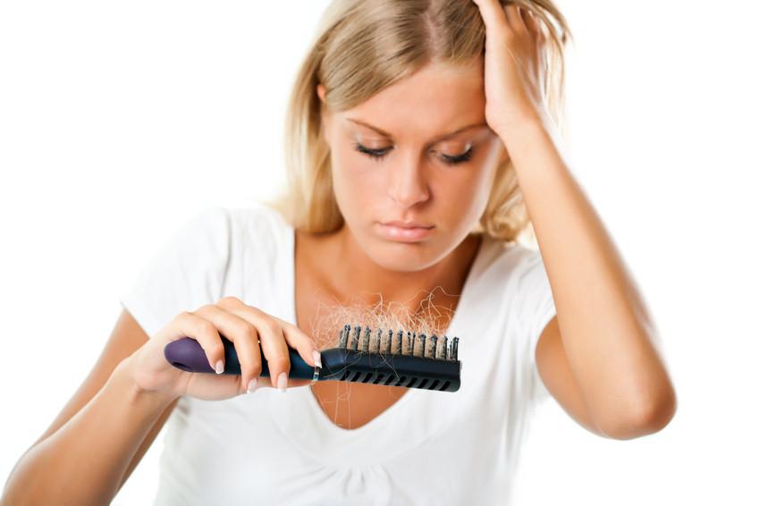Blinde Frau mit schwarzem Kamm in der Hand und Haarausfall