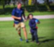Teacher and student running with footbal