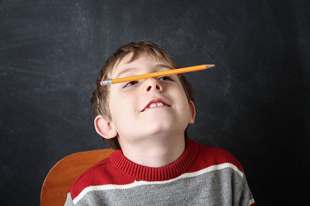 Young bored boy balancing a pencil on hi
