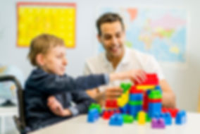 Young boy in wheelchair building colorful blocks during therapy session with male therapist smiling