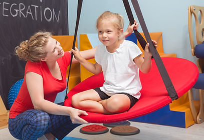 Therapist and child on therapy swing