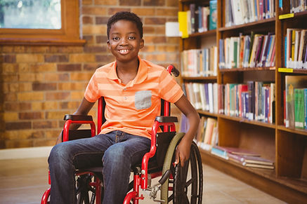 Young boy in red wheelchair smiling in a library setting