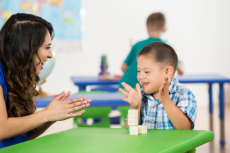 Young boy with Down syndrome clapping with woman for building with blocks during therapy session
