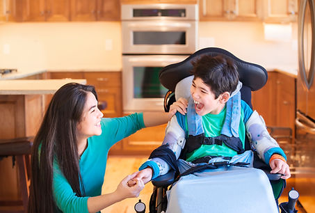 Young boy in wheelchair smiling and holding hands with caregiver who is a young woman
