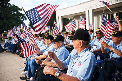 Group of Veterans sitting and waving american flags