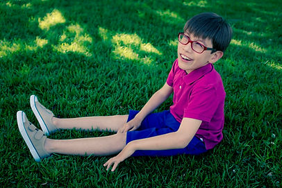 Young boy with disabilities sitting in the grass smiling