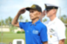 U.S. Navy Veteran saluting and wearing U.S. Navy polo shirt and cap