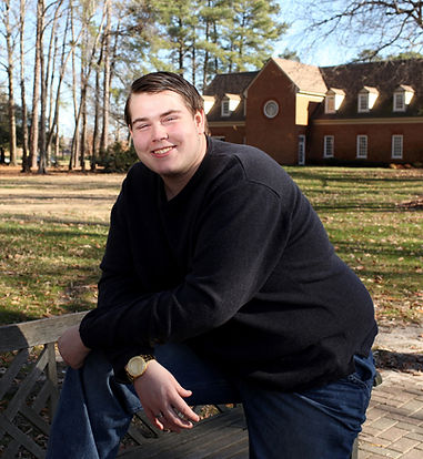 Man with a disability leaning on a bench and smiling in an outdoor setting