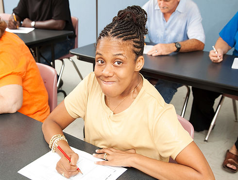 Young Woman in Classroom with pencil and paper smiling