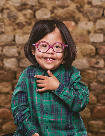 Young girl with a disability smiling with pink glasses on