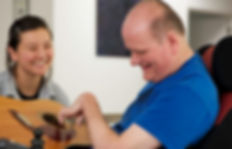 Man with a disability learning to play guitar from young woman