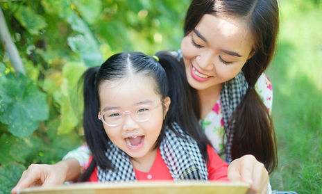 Mother and daughter reading a book and smiling in an outdoor setting