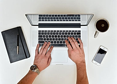hands on laptop with coffee and mobile phone
