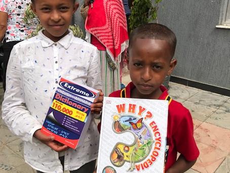 Community children celebrate good school reports.