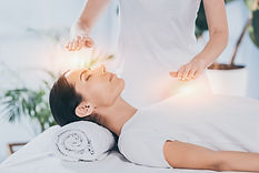 side view of calm young woman receiving reiki healing therapy on head and chest .jpg