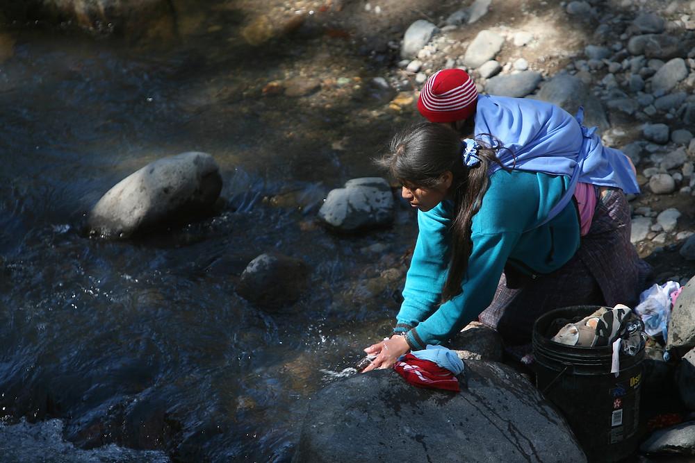 Foto: Sean Hawyek. Una joven mujer con su bebé en un río en Guatemala
