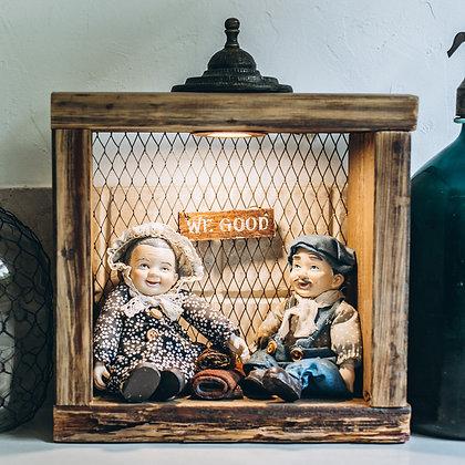 בובות מקרמיקה בתוך קובית עץ אורן ורשת ברזל פנימית