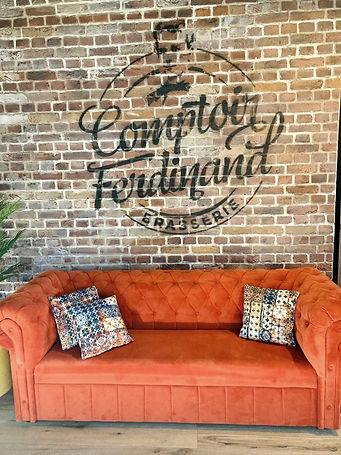 Photo entrée de chez Comptoir Ferdinand, canapé orange, coussin colorés et logo peint sur mur de briques rouges