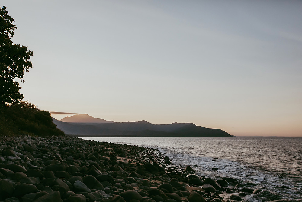 the last of the sunshine peeking through the hills over the ocean.  Just out of Port Douglas, Queensland.
