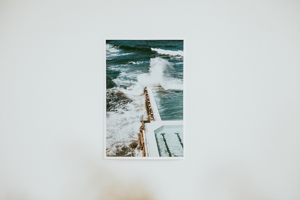 a wave crashes over the corner of the iconic Bondi Icebergs rockpool, Bondi Beach, Sydney.