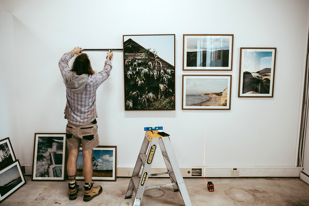 Scott hanging the photographs, tape measure in hand, getting the levels just right!