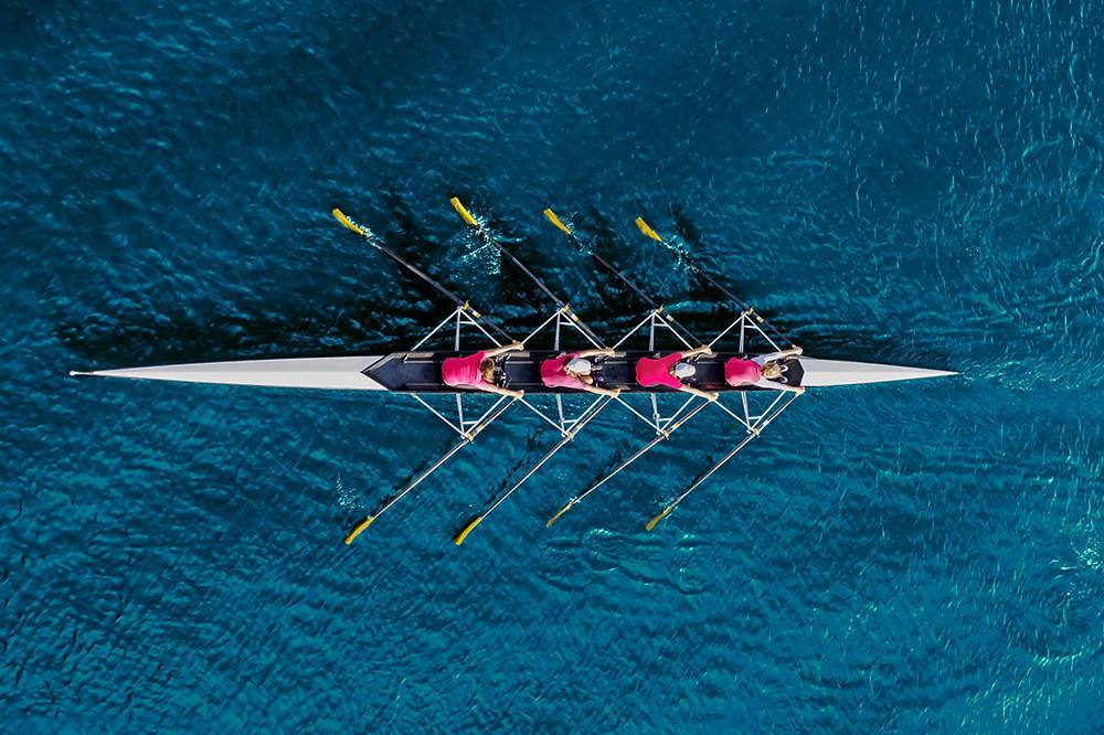 Female rowing team on blue water