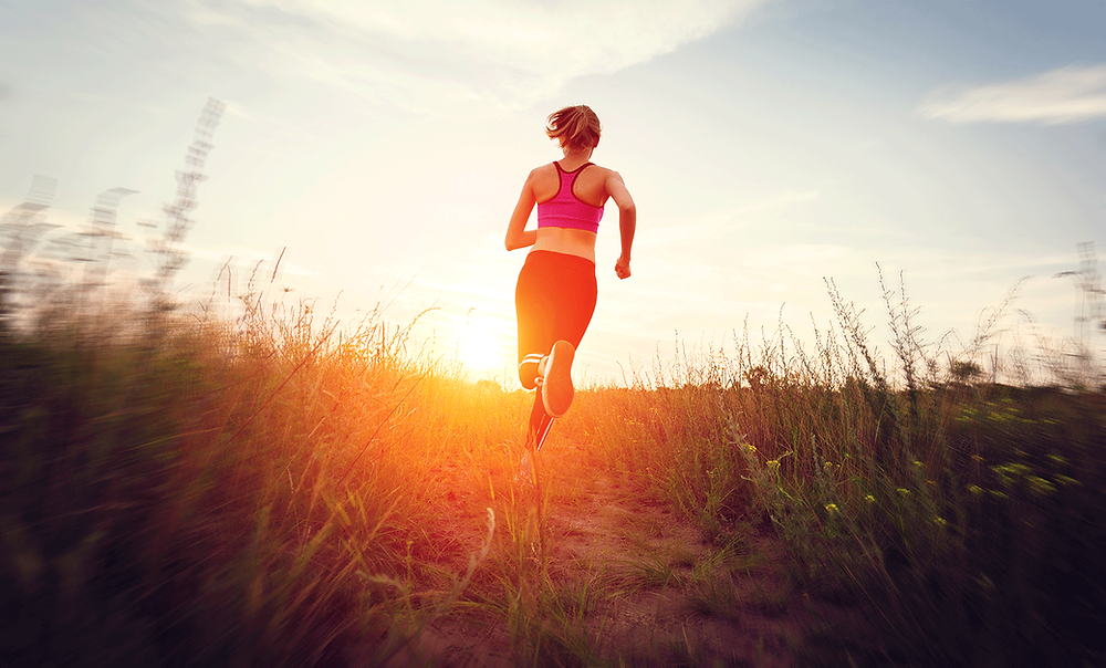 Girl running into the sunset on a grass trail