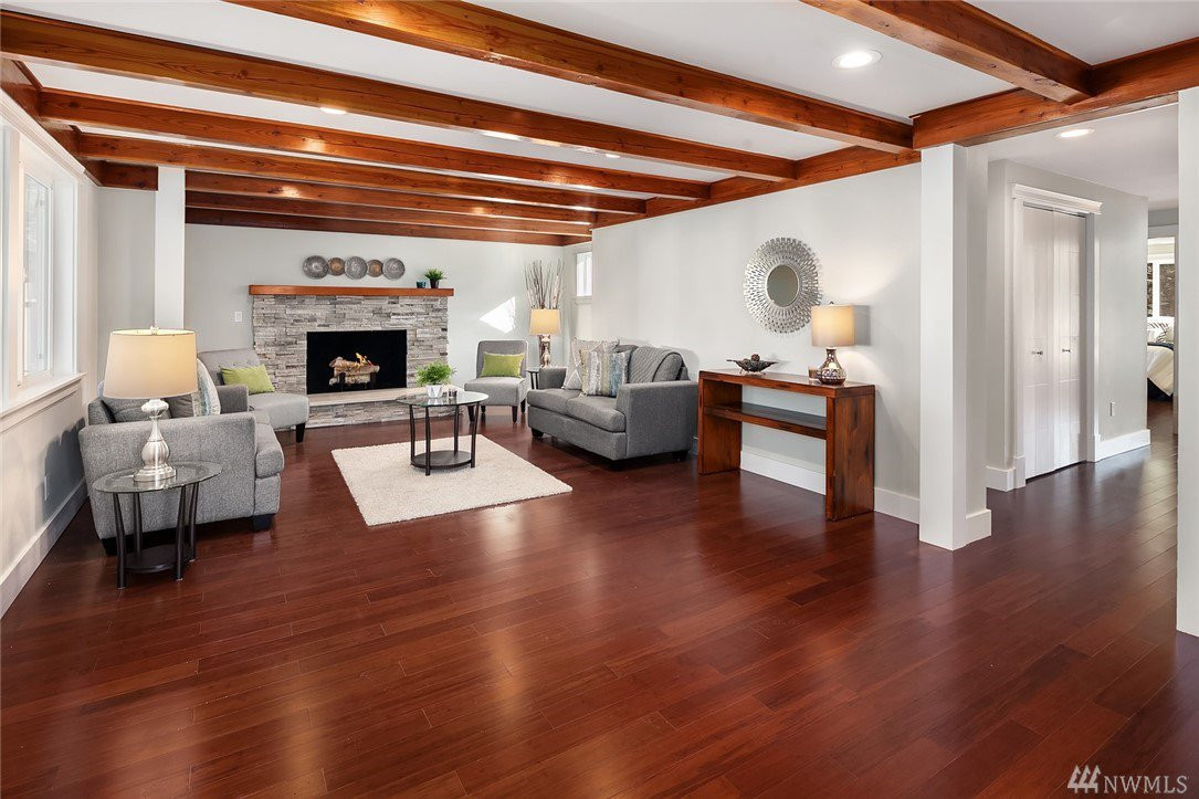 Stunning living room w/ amazing hardwoods, exposed ceiling beams & cozy fireplace.
