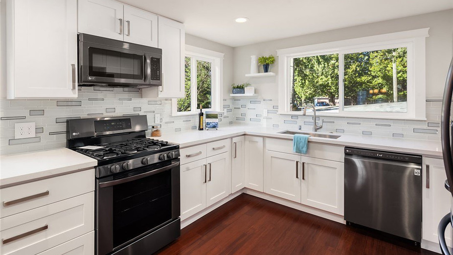 Beautiful kitchen w/ quartz counters & eating bar overlooking the formal dining room.
