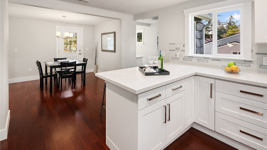 Beautiful kitchen w/ quartz counters & eating bar overlooking the formal dining room w/ direct access to the huge, private deck & backyard – perfect for fun & entertaining.
