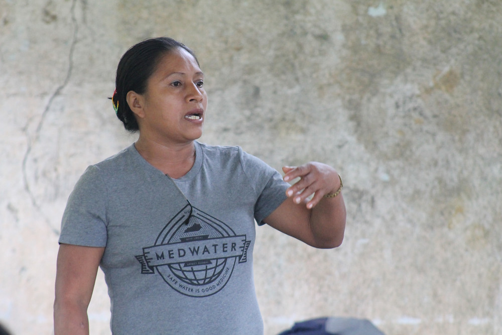 Lucilla teaches a community about safe water, hygiene, and sanitation.