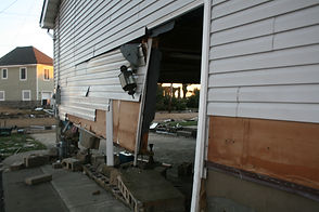 Side of a house with a hole torn through it and damaged siding