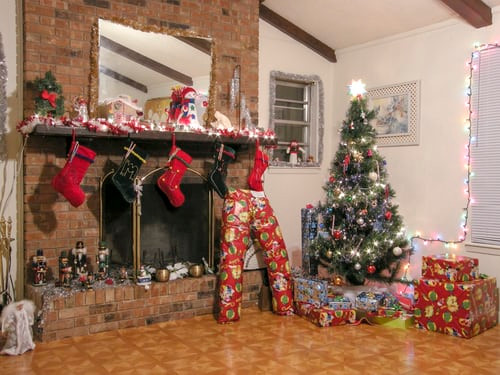 fireplace decorated with stockings , surrounded by Christmas tree and wrapped presents
