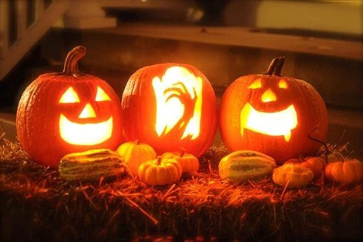 three carved pumpkins with light inside, happy face, scary hand, scary face
