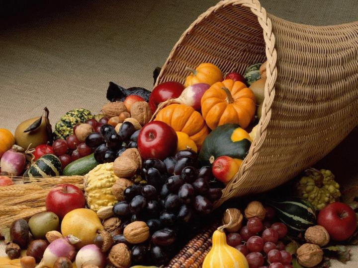 Wicker cornucopia filled with gourds, fruit and nuts