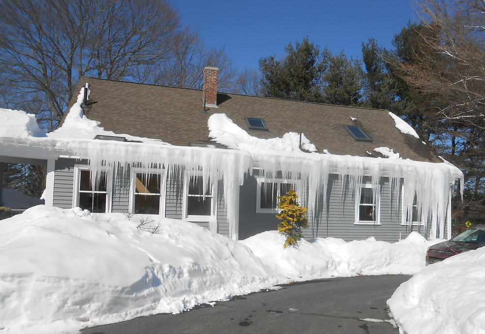 grey house with piled snow and icicles hanging from the roof