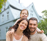 A happy mother, father and daughter in front of a house