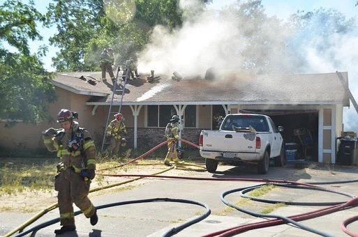 House with smoke coming from the roof with firemen in front and a pickup truck in the driveway.