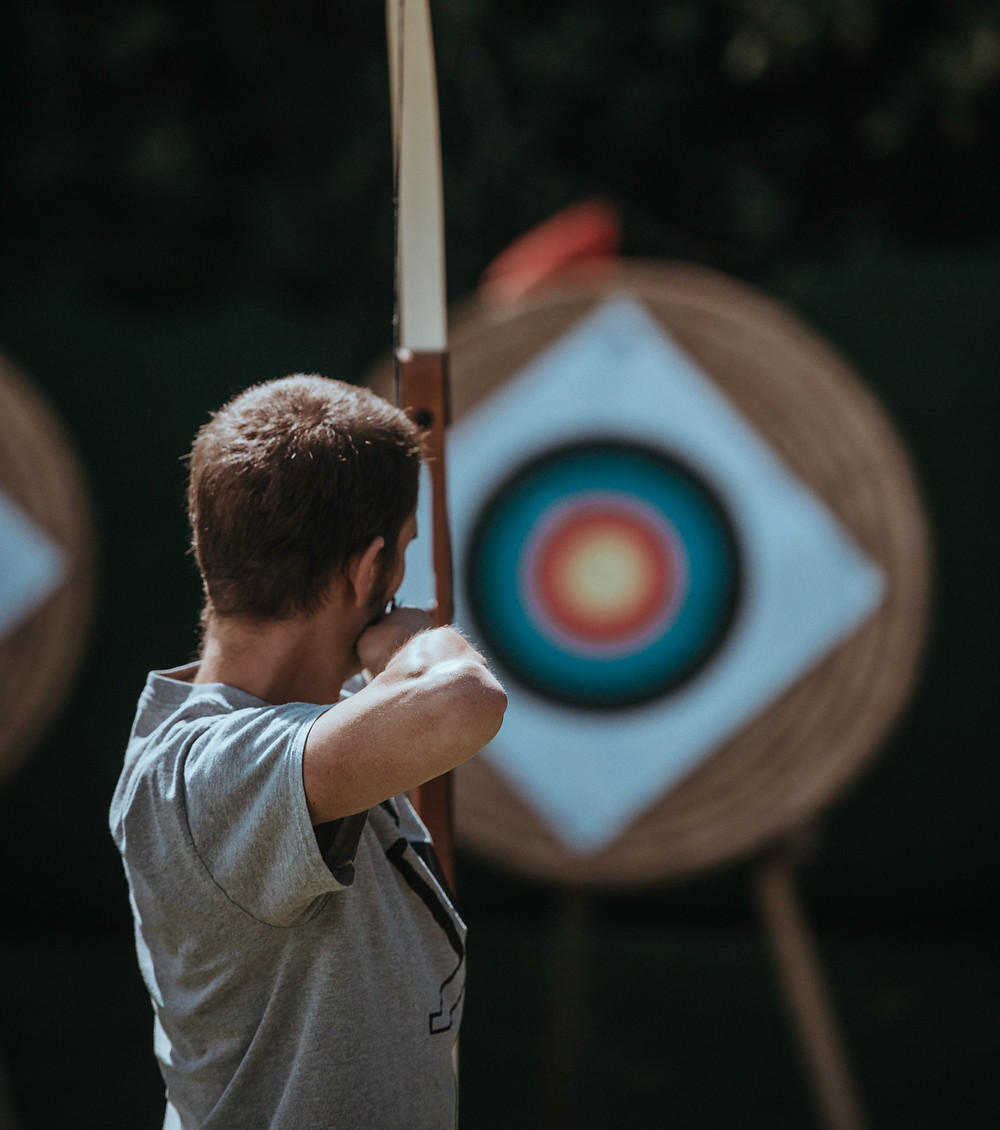 Chase the scores and bid with confidence. Picture of an archer shooting at a target.