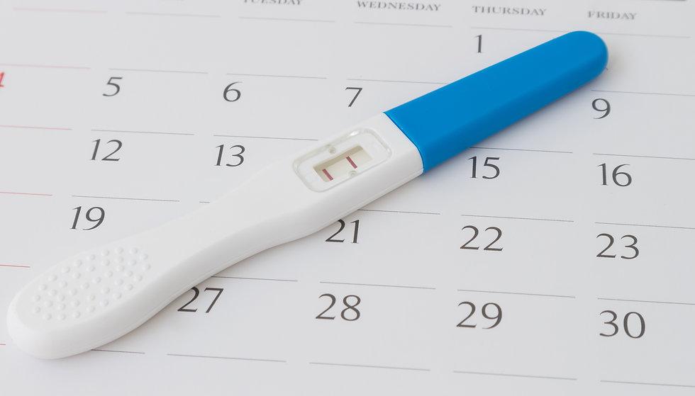 Pregnancy test on calendar background, h