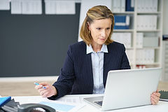 Attractive middle-aged businesswoman sit