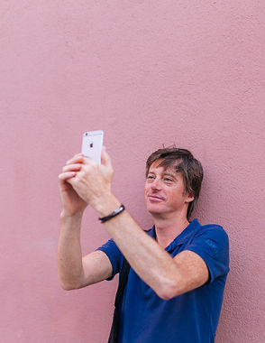 man-taking-selfie-while-leaning-on-wall-