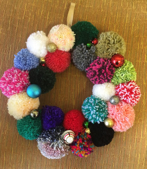 Creating Christmas wreaths from pom poms made during the session