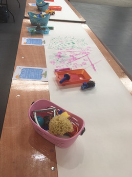 Paint along with different objects to use to make a mark