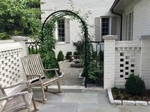 hidden garden, pierced brick walls with limestone caps; wrought iron arch with climbing rose