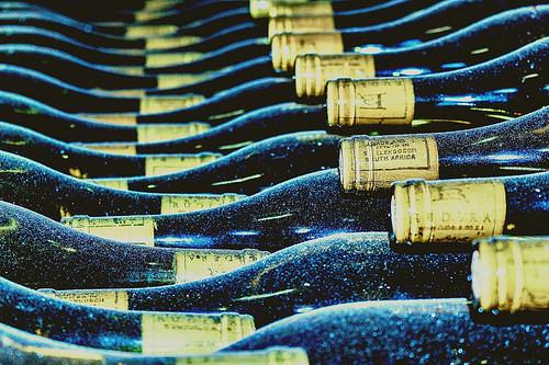 貯蔵庫に並ぶ埃を被ったワインの瓶