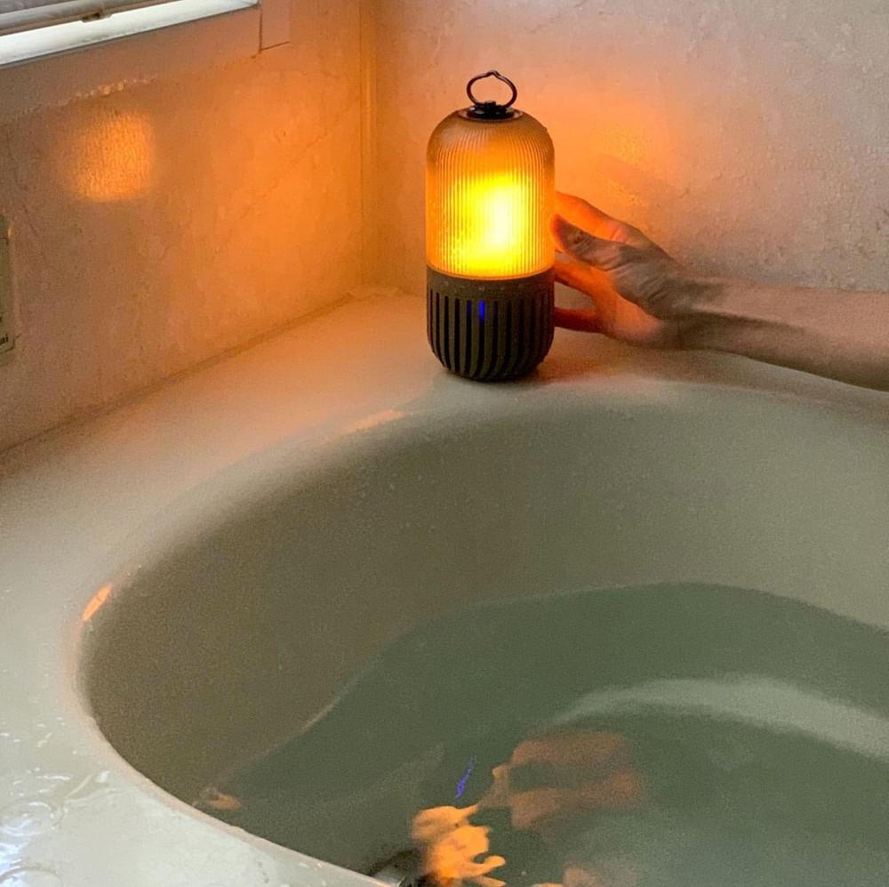 SPICE OF LIFE ゆらぎカプセルスピーカーが浴槽の隅に置かれてオレンジ色に光っているところ