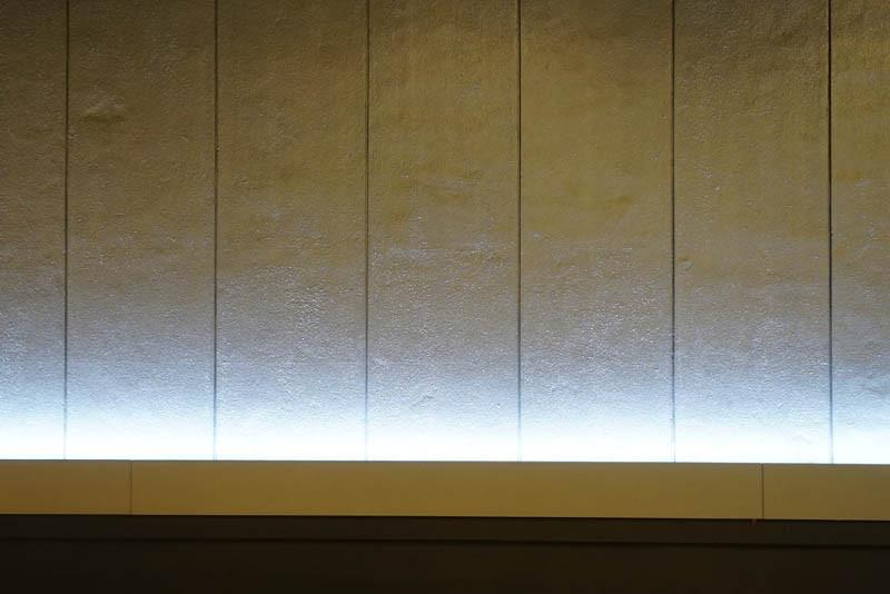 壁に浮かび上がる淡い水色の間接照明