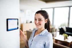 a-woman-looking-at-tablet-with-smart-home-screen-P6MF72K.jpg