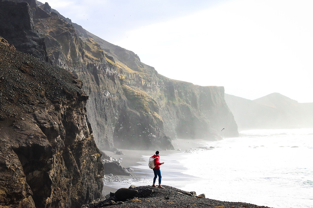 a woman look up at some cliffs at the coast line, the air is full of sea mist